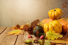 Υπόβαθρο εποχής φθινοπώρου με τα φύλλα πτώσης και κολοκύθα στον ξύλινο πίνακα Στοκ εικόνα με δικαίωμα ελεύθερης χρήσης