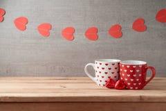 Υπόβαθρο ημέρας βαλεντίνου με τα φλυτζάνια καφέ, τη σοκολάτα μορφής καρδιών και τη γιρλάντα στοκ εικόνες