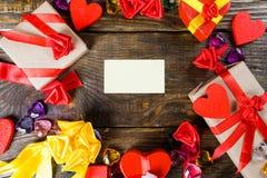 Υπόβαθρο ημέρας βαλεντίνων ` s με την κάρτα χαιρετισμών, τις διακοσμήσεις καρδιών και τα μικρά δώρα στον ξύλινο πίνακα Τοπ άποψη  Στοκ φωτογραφίες με δικαίωμα ελεύθερης χρήσης