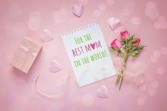 Υπόβαθρο ημέρας μητέρων με το μήνυμα, τα ρόδινα τριαντάφυλλα και το κιβώτιο δώρων επάνω στοκ φωτογραφία