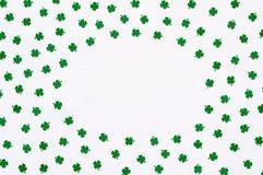 Υπόβαθρο ημέρας του ST Πάτρικ με τα πράσινα quatrefoils στο άσπρο υπόβαθρο, στρογγυλά σύνορα πλαισίων στοκ φωτογραφίες