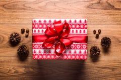 Υπόβαθρο θέματος Χριστουγέννων, παρόν Χριστουγέννων και κώνοι πεύκων στον ξύλινο πίνακα Στοκ φωτογραφίες με δικαίωμα ελεύθερης χρήσης