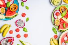 Υπόβαθρο θερινού καθαρό και υγιές τρόπου ζωής με τα διάφορα ζωηρόχρωμα τεμαχισμένα τροπικά φρούτα και τα πιάτα μούρων στοκ φωτογραφία