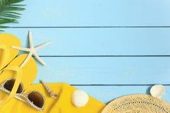 Υπόβαθρο θερινών διακοπών με την κίτρινη πετσέτα παραλιών, τις πτώσεις κτυπήματος, τα γυαλιά ηλίου, το φύλλο φοινικών και τα θαλα στοκ εικόνες