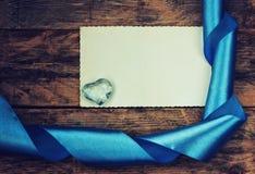Υπόβαθρο διακοπών ημέρας βαλεντίνου, καρδιά γυαλιού, μπλε κορδέλλα Στοκ Εικόνες