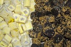 Υπόβαθρο - κομμάτια του lokum rahat στα τσιπ καρύδων και στο λούστρο σοκολάτας με το σουσάμι Στοκ εικόνες με δικαίωμα ελεύθερης χρήσης