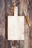Υπόβαθρο κουζινών με τον κενούς παλαιούς ξύλινους τέμνοντες πίνακα και το μαχαίρι στοκ εικόνες