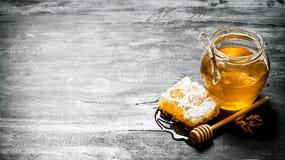 Υπόβαθρο μελιού Φυσική χτένα μελιού και ένα βάζο γυαλιού Στοκ φωτογραφίες με δικαίωμα ελεύθερης χρήσης