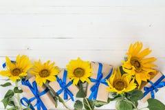 Υπόβαθρο με μια ανθοδέσμη των κίτρινων WI ηλίανθων και κιβωτίων δώρων Στοκ Εικόνες