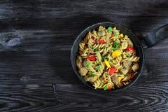 Υπόβαθρο με τα ζυμαρικά με το κρέας και λαχανικά στη μαύρη κατσαρόλλα Στοκ Φωτογραφία