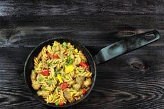 Υπόβαθρο με τα ζυμαρικά με το κρέας και λαχανικά στη μαύρη κατσαρόλλα Στοκ εικόνα με δικαίωμα ελεύθερης χρήσης