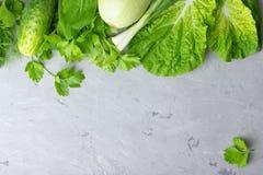 Υπόβαθρο με τα πράσινα λαχανικά, τη σαλάτα, το αγγούρι, το πράσινα κρεμμύδι και τα κολοκύθια στην γκρίζα επιτραπέζια κορυφή πετρώ στοκ φωτογραφία με δικαίωμα ελεύθερης χρήσης