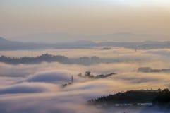 Υπόβαθρο με τα πυκνά αγροκτήματα κάλυψης ομίχλης και δάσος στο μέρος 21 αυγής στοκ φωτογραφία