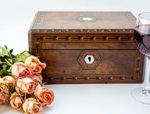 Υπόβαθρο με τα ρόδινα ξηρά τριαντάφυλλα, παλαιό πνεύμα κιβωτίων κοσμήματος ξύλων καρυδιάς Στοκ Φωτογραφίες