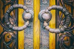 Υπόβαθρο με τα στοιχεία σφυρηλατημένων κομματιών, λαβές μετάλλων υπό μορφή δαχτυλιδιών στις ξύλινες πόρτες στοκ εικόνες