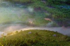 Υπόβαθρο με την πυκνή ομίχλη και μαγικό φως στην ανατολή Το αγρόκτημα καφέ και τα μικρά σπίτια στο λαμπρό μέρος 11 ηλιοφάνειας στοκ εικόνες