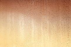 Υπόβαθρο με τις πτώσεις στο γυαλί, λεκιασμένος κίτρινος-καφετής Στοκ εικόνες με δικαίωμα ελεύθερης χρήσης