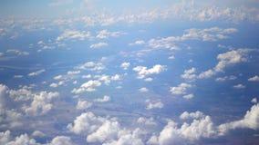 Υπόβαθρο μπλε ουρανού και σύννεφων έξω από το αεροπλάνο επιβατών, που πετά μέσω των σύννεφων - η άποψη μέσω του παραθύρου, ακολου απόθεμα βίντεο