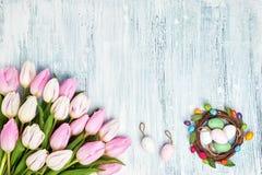 Υπόβαθρο Πάσχας με τα διακοσμητικά αυγά και τις ρόδινες τουλίπες Κάρτα διακοπών με το διάστημα αντιγράφων στο ανοικτό μπλε υπόβαθ Στοκ εικόνες με δικαίωμα ελεύθερης χρήσης