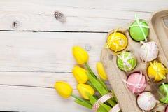 Υπόβαθρο Πάσχας με τα ζωηρόχρωμα αυγά και τις κίτρινες τουλίπες Στοκ εικόνες με δικαίωμα ελεύθερης χρήσης