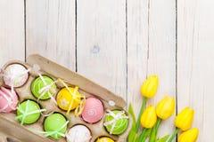 Υπόβαθρο Πάσχας με τα ζωηρόχρωμα αυγά και τις κίτρινες τουλίπες Στοκ φωτογραφία με δικαίωμα ελεύθερης χρήσης