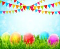 Υπόβαθρο Πάσχας με τα ζωηρόχρωμα αυγά στην πράσινες χλόη και τις σημαίες Στοκ Φωτογραφίες