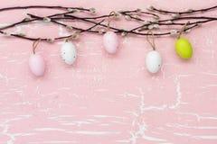 Υπόβαθρο Πάσχας με τα διακοσμητικά αυγά και κλάδος ιτιών στο ρόδινο υπόβαθρο Στοκ Εικόνα