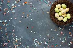 Υπόβαθρο Πάσχας με τη φωλιά Πάσχας, τα αυγά καραμελών σοκολάτας και το αυγό Στοκ Εικόνες