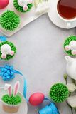 Υπόβαθρο Πάσχας με το λαγουδάκι cupcakes, το τσάι και τα χρωματισμένα αυγά στοκ φωτογραφίες