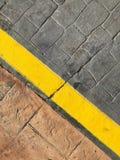 Υπόβαθρο πεζοδρομίων - κίτρινη γραμμή στα σύνορα οδικών οδών στοκ εικόνες