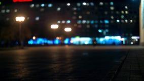 Υπόβαθρο πόλεων τη νύχτα με τα αυτοκίνητα Από την εστίαση το υπόβαθρο με μουτζουρωμένο τα φω'τα πόλεων φιλμ μικρού μήκους