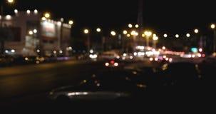 Υπόβαθρο πόλεων τη νύχτα με την κίνηση των αυτοκινήτων Από την εστίαση το υπόβαθρο με μουτζουρωμένο τα φω'τα πόλεων φιλμ μικρού μήκους