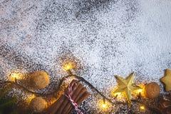 Υπόβαθρο συνόρων Χριστουγέννων με την κανέλα, τα φω'τα της γιρλάντας και τα ξύλα καρυδιάς Στοκ Φωτογραφία