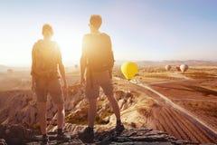 Υπόβαθρο ταξιδιού, ζεύγος των ταξιδιωτών που εξετάζουν την πανοραμική θεαματική όμορφη άποψη των βουνών Στοκ Φωτογραφίες