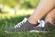 Υπόβαθρο της γυναίκας στα νέα παπούτσια γυμναστικής με τις άσπρες δαντέλλες στον πράσινο χορτοτάπητα στη χλόη Στοκ Εικόνες