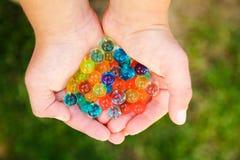 Υπόβαθρο της Νίκαιας των διαφορετικών σφαιρών χρωμάτων στα χέρια στοκ φωτογραφία