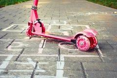 Υπόβαθρο της παιδικής χαράς με το ρόδινα μηχανικό δίκυκλο και το hopsco παιδάκι Στοκ Φωτογραφίες