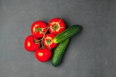 Υπόβαθρο του κενού μαύρου χρώματος με τα φρέσκα υγιή λαχανικά - αγγούρι και ντομάτες Τοπ όψη Στοκ Εικόνες