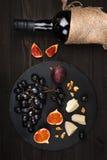 Υπόβαθρο τροφίμων με το κόκκινο κρασί, τα σύκα, τα σταφύλια και το τυρί Στοκ Εικόνες