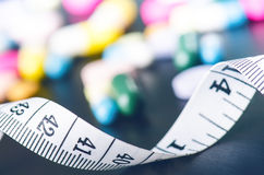 Υπόβαθρο φαρμακείων σε έναν μαύρο πίνακα με τη μέτρηση της ταινίας μαύρες ταμπλέτες ανασκόπησης Χάπια Ιατρική και υγιής στενό πισ Στοκ Εικόνες