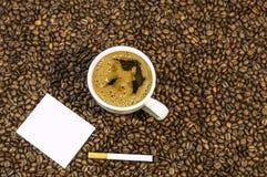 Υπόβαθρο φασολιών καφέ με το φλυτζάνι του φρέσκου καυτού καφέ και πούρο με την άσπρη κάρτα Στοκ φωτογραφία με δικαίωμα ελεύθερης χρήσης