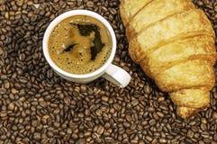 Υπόβαθρο φασολιών καφέ με το φλυτζάνι του φρέσκου καυτού καφέ και croissant Στοκ Εικόνα