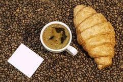 Υπόβαθρο φασολιών καφέ με το φλυτζάνι του φρέσκου καυτού καφέ και croissant Στοκ εικόνες με δικαίωμα ελεύθερης χρήσης