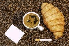 Υπόβαθρο φασολιών καφέ με το φλυτζάνι του φρέσκου καυτού συνόλου καφέ και πιάτων των μπισκότων Στοκ εικόνες με δικαίωμα ελεύθερης χρήσης