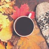 Υπόβαθρο φθινοπώρου με τα φύλλα colordul και το καυτό φλυτζάνι καφέ φωνάξτε Στοκ Εικόνες
