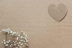 Υπόβαθρο χαρτονιού με τις καρδιές και τα μικρά άσπρα λουλούδια διάστημα Στοκ Εικόνα