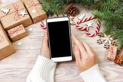 Υπόβαθρο Χριστουγέννων: θηλυκά χέρια που γράφουν στο ανοιγμένο smartphone με το διάστημα αντιγράφων στον αγροτικό ξύλινο πίνακα π Στοκ εικόνες με δικαίωμα ελεύθερης χρήσης