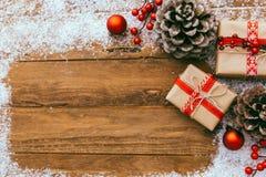 Υπόβαθρο Χριστουγέννων - κιβώτιο δώρων χριστουγεννιάτικου δώρου και διακόσμηση των στοιχείων στο ξύλινο υπόβαθρο Στοκ Εικόνες