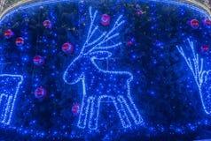 Υπόβαθρο Χριστουγέννων με ένα ελάφι και τις γιρλάντες στοκ εικόνα