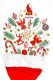 Υπόβαθρο Χριστουγέννων με ένα καπέλο santa από το οποίο διεσπαρμένα δώρα, καραμέλα, νέα παιχνίδια διακοσμήσεων έτους σε ένα άσπρο Στοκ φωτογραφία με δικαίωμα ελεύθερης χρήσης